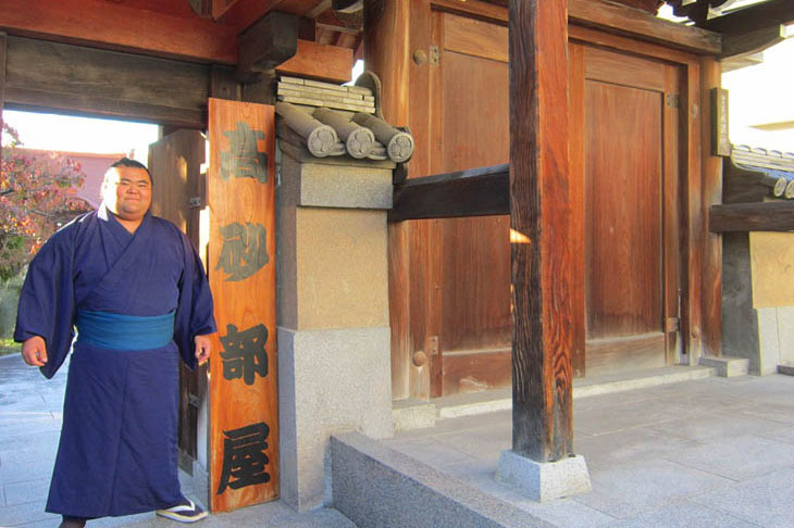 """This is the entrance to Jodoji Temple in Tojinmachi in Fukuoka City, where the Takasago Stable, a sumo stable, stays during the Kyushu Grand Tournament. A sumo wrestler in a blue kimono stands next to a board with the words """"Takasago Beya"""" written in large letters."""