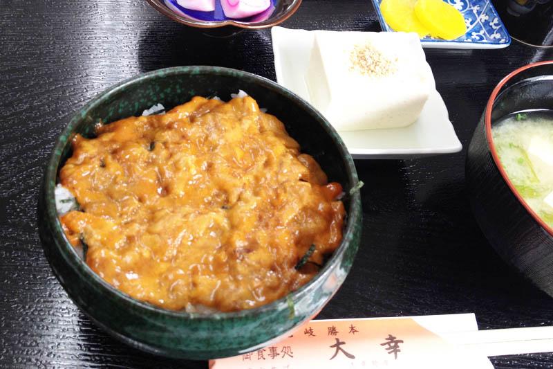 """Ini adalah """"Uni-don"""" dengan bulu babi, spesialisasi Iki. Semangkuk nasi di atasnya dengan banyak bulu babi mentah berwarna kekuningan."""
