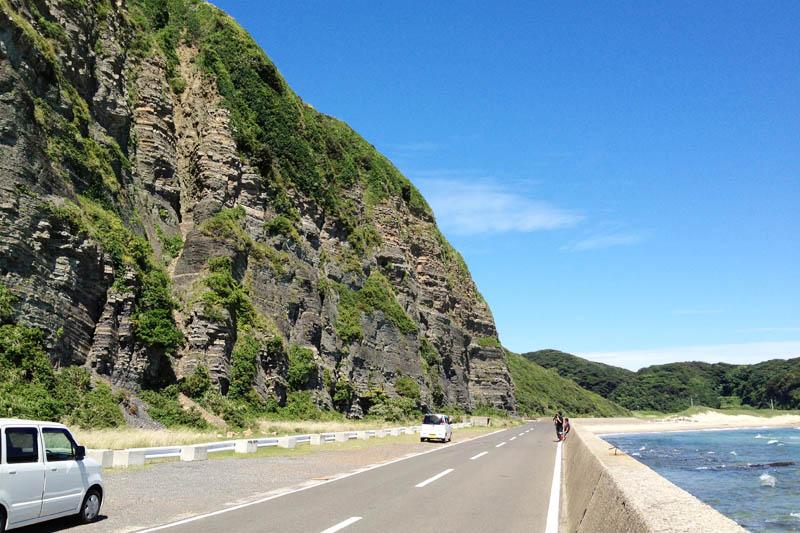 """Sisi kiri jalan adalah tebing yang disebut """"Iki Dodai Ishi"""", Batu Yayasan Iki. Terdapat lapisan lapisan sedimen yang terdiri dari serpih dan batupasir. Di sebelah kanan jalan adalah pantai"""