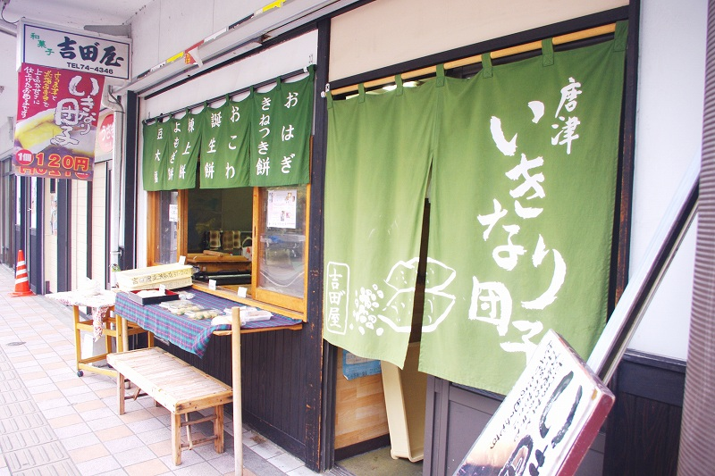 This is the exterior of a Japanese sweets shop in Karatsu called Yoshida-ya, famous for its Ikinari-dango. The entrance and windows of the store are covered with green curtain.