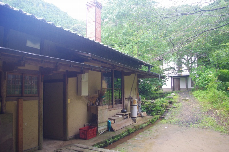 It is the workshop of Ryuta-kiln with the chimney of the kiln for baking ceramic wares and surrounded by green trees.