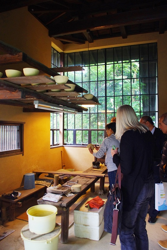 This is the inside of the workshop of Nakazato Taroemon of Karatsu ware. The room has a high ceiling and large windows, and the shelves are filled with pottery that has been made. Some visitors from overseas are listening to the explanation from the craftsman.