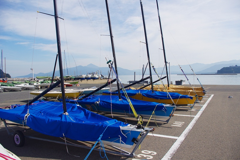 The Saga Prefecture Yacht Harbor is located in Karatsu City. In the boat park, there are several dinghies covered with blue covers.