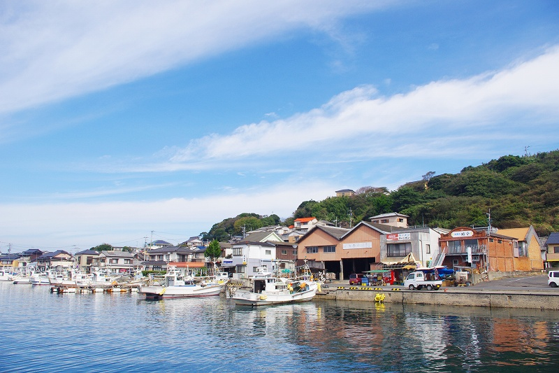 Yobuko fishing port. There are several fishing boats anchored in the harbor. Dried fish shops and houses are lined up.