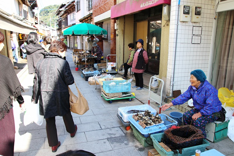 At the morning market in Yobuko, local fishermen and farmers sell fresh seafood and vegetables on the street.