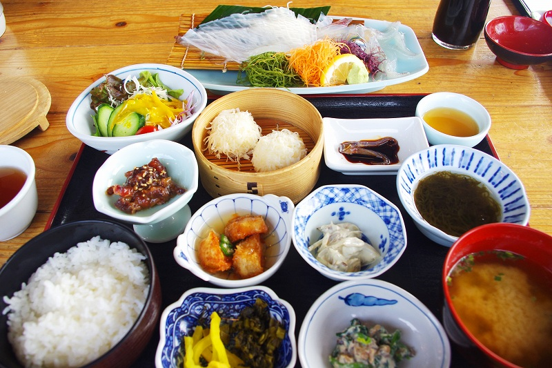 This is the Live Squid Set Meal at Ika Honke Honten, a recommended squid restaurant in Yobuko, Karatsu. The dish includes live squid sashimi, squid siumai, mozuku seaweed, simmered vegetables, raw vegetables, rice, and miso soup.