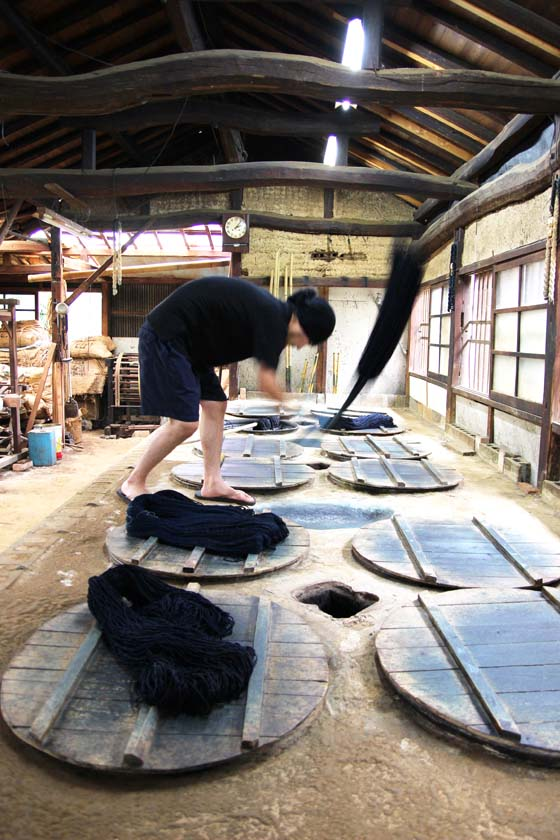 At the Indigo Dyeing Atelier Takeshi Yamamura, the indigo-dyed threads are being tapped into the hollows between the jars in order to better color them.
