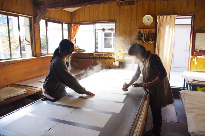 This is the Matsuo Washi Workshop in Yame. Two women are drying freshly made, damp washi on a heated table.