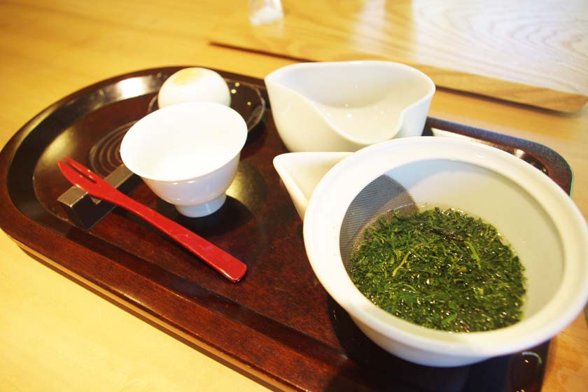This is gyokuro, a high-grade green tea at Seisui-an. On the right is a teapot filled with gyokuro, and on the left is a teacup. White Japanese sweets are placed behind the tea bowl.